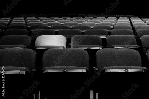 Image of rows of seats with a spotlight on one