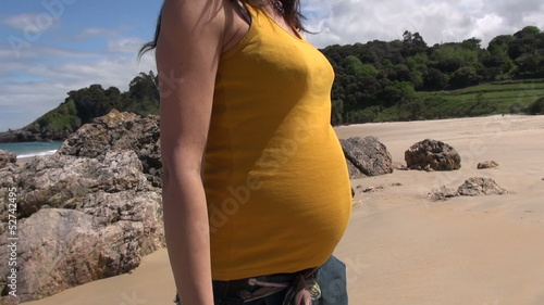 yellow belly pregnant walking at beach