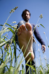 young man bare feet on green grass