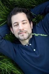 beautiful young man lying on green gras
