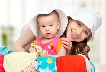 Mom and baby girl with suitcase and clothes ready for traveling