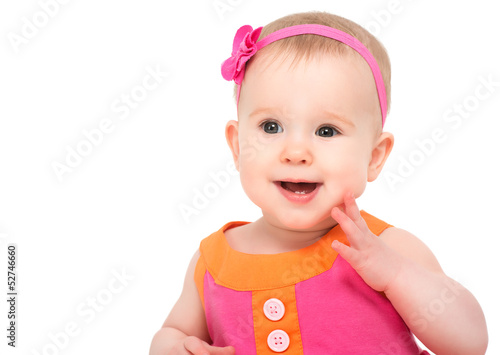 happy little sly baby girl in bright multicolored festive dress