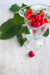 juicy red berry cherry in the glass beaker and green leafs