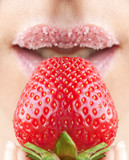 Woman's mouth with red strawberry covered with sugar
