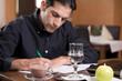 Mann bei Schreibarbeit in Restaurant