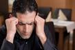 Mann mit Kopfschmerzen im Restaurant