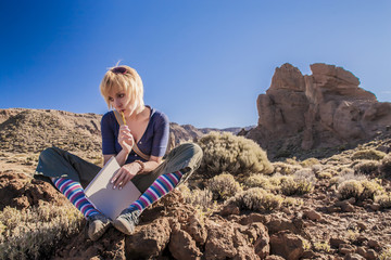 Girl is sitting on the rock and thinking with notebook