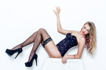 Sexy woman in black stockings and corset, legs up, high heels
