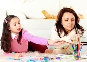 Beautiful girl draws with his mother