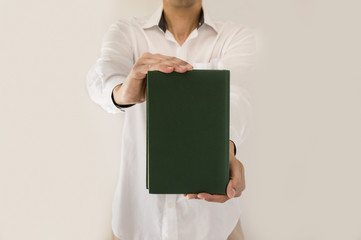 man holding up book with green empty book cover in close-up