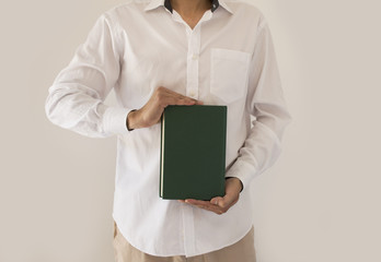 man holding up book with green empty book cover