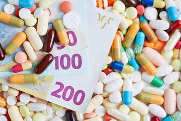 Euroscheine liegen auf Pillen und Tabletten