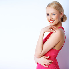 Lovely blond woman smiling while posing on white