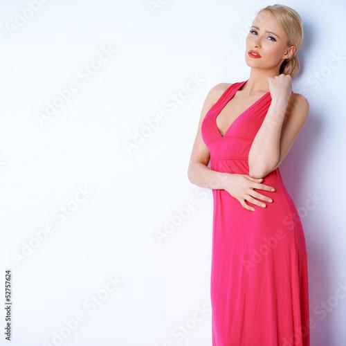 Sensual blond woman posing in pink dress