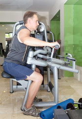 man is engaged in training in fitness center in a gym