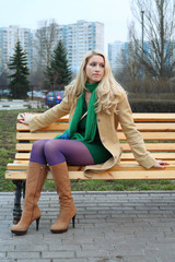 Cute girl in purple tights sitting on a bench.