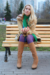 girl with red nails in purple tights sitting on bench.