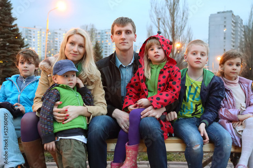 Big happy family in the evening sitting on the bench.