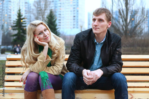 Romantic young couple sitting on bench at evening.