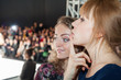 Two beautiful girls watching a fashion show.