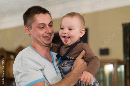 Son shows tongue sitting on the arms of his father.