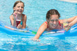 Happy mother and daughter swimming in pool with drink in hand