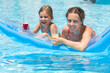 mother and daughter swimming in pool on inflatable mattress