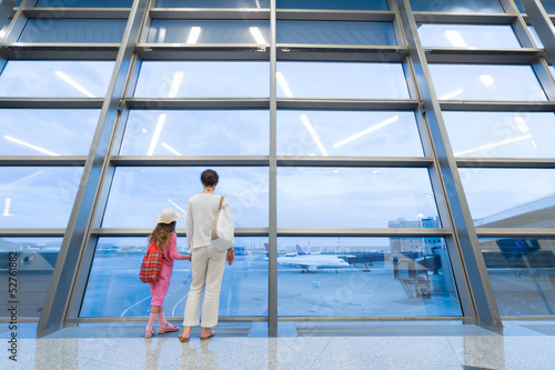 Mother and daughter looking out window at airport terminal