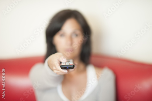 Young woman with remote watching TV.