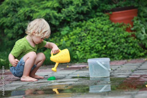 White little barefoot girl playing with water