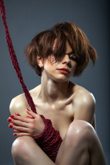 Portrait of passionate red-haired girl with rope