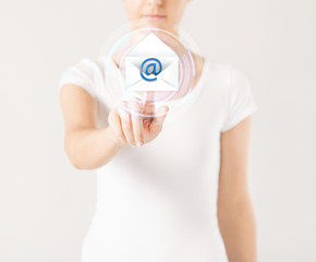 woman pressing virtual button with e-mail icon