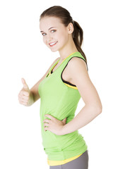 Fitness woman in sport clothes gesturing thumbs up