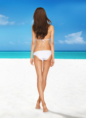 model posing in white bikini on the beach