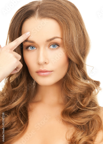 beautiful woman pointing at her forehead