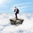 Happy businessman above clouds
