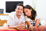 Asian couple at home in their living room