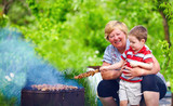 happy grandmother with grandchild roasting meat on picnic
