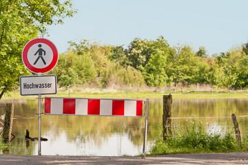 Schild Hochwasser - mit Absperrbake - Himmel blau
