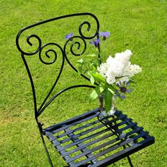 eleganter Stuhl mit Flieder im Garten