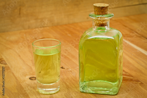Peppermint liqueur bottle and shot on wooden background