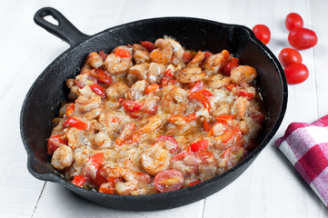 Cooking shrimp and cherry tomatoes in skillet