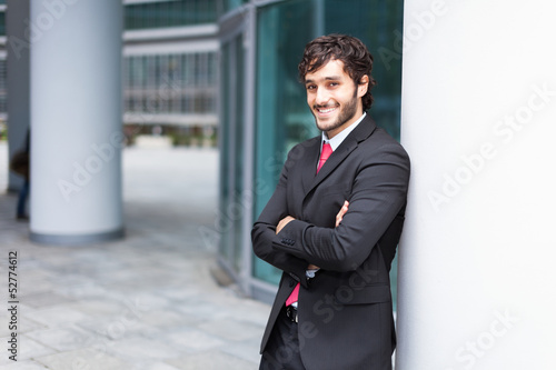 Businessman leaning on a column