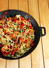 Noodles with vegetables on wok on wooden background