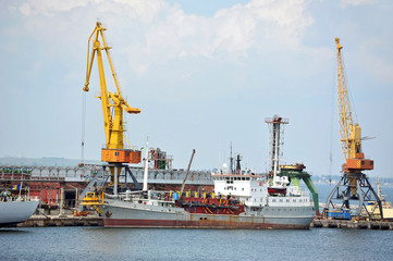 Industrial ship under crane bridge in harbor