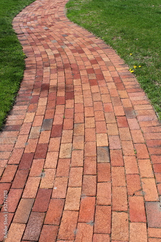 Patterned brick walkway in landscaped lawn