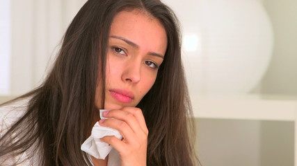 Sick Hispanic woman with tissue in hand