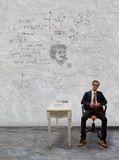 man sitting on desk and physic formula on wall poster