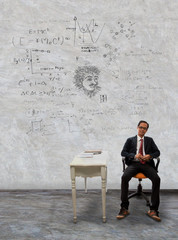 man sitting on desk and physic formula on wall