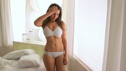 Mexican woman in underwear standing in window